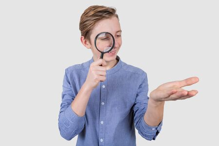 Smiling Teenager with Magnifying Glass looking at something imaginary in his hand Isolated on the white background .