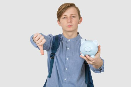 Sad Teenager boy holding piggy bank  with thumb down signs over white background. Financial education savings concept. Stok Fotoğraf
