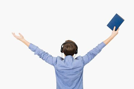 Happy student listening to music and holding book with arms raised in air over white background. Young boy student relaxing  listening  to music with rised hands. Freedom concept.
