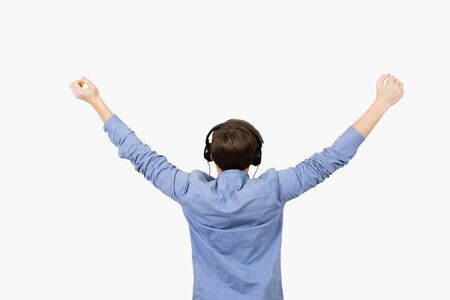 Happy student listening to music with arms raised in air over white background. Young boy student relaxing  listening  to music with rised hands. Freedom concept. Stok Fotoğraf