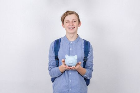 Smiling Teenager boy holding piggy bank over white background. Financial education savings concept. Stok Fotoğraf