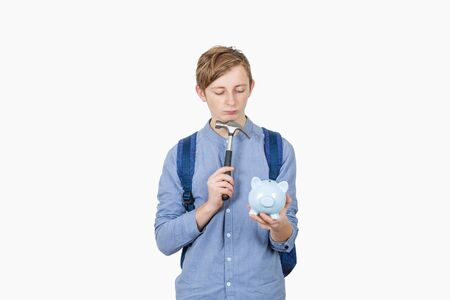 Frustrated student boy having doubt breaking his piggy bank using a hammer isolated over white background. Small amount of financial savings, not enough money for study contract.
