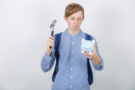 Frustrated student boy try to break a piggy bank using a hammer isolated over white background. Small amount of financial savings, not enough money for study contract.
