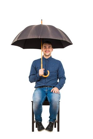 Full length of joyful businessman seated on chair standing under his open umbrella looking happy and confident to camera isolated on white background.