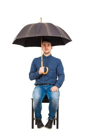 Full length of confident businessman seated on chair standing under his open umbrella looking to camera isolated on white background.