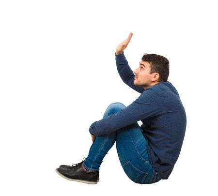 Side view scared young man introvert seated on the floor keeps hands raised to protect him from any danger, isolated over white background. Helpless guy victim of bullying or abuse.