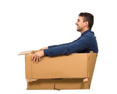Full length side view of joyful childish man sitting inside a cardboard box isolated over white background. Stok Fotoğraf