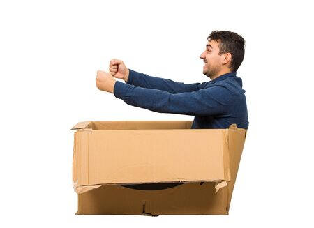 Full length side view of childish man sitting inside a cardboard box pretending to drive a new car isolated over white background. Joyful guy dreaming of buying a personal vehicle.