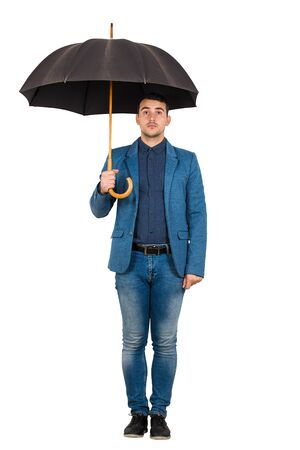 Ritratto integrale dell'uomo d'affari che indossa vestito blu casuale che sta sotto l'ombrello aperto che sembra perplesso alla macchina fotografica isolata sopra fondo bianco.