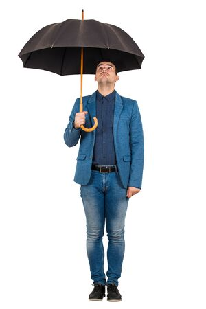 Full length portrait of confused businessman standing under open umbrella looking up perplexed isolated over white background. Stok Fotoğraf