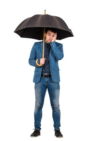 Full length portrait of upset and thoughtful businessman standing under open umbrella keeps palm to face looking down confused isolated over white background.