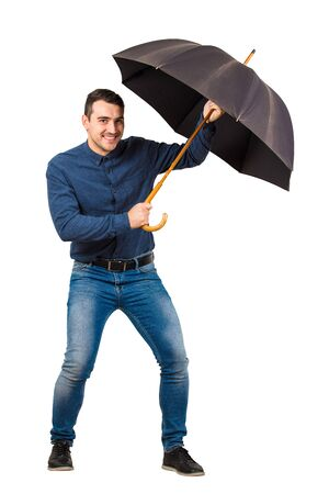 Full length of cheerful businessman hiding behind his open umbrella as a shield to protect of any danger isolated on white background. Business concept of facing adversity and auto defending.