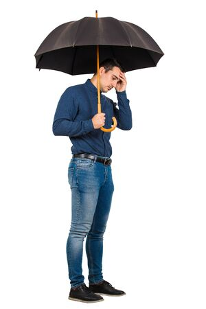 Full length of depressed businessman standing under his open umbrella hand to forehead isolated on white background. Man suffering headache and anxiety.