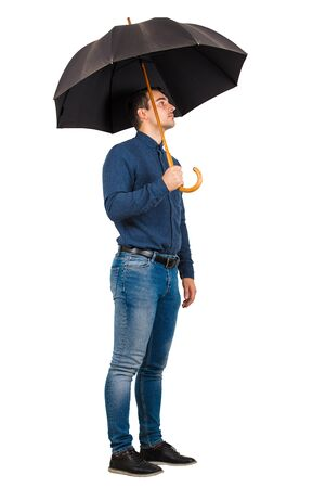 Side view full length of confident businessman standing under his open umbrella looking hopeful ahead isolated on white background.