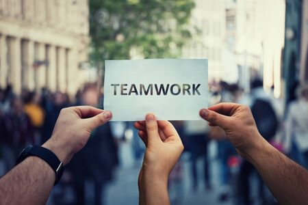 Diverse hands holding together a paper with teamwork text. Group of three people unity and team concept as business metaphor for joining powers. Partnership cooperation symbol, working collaboration.