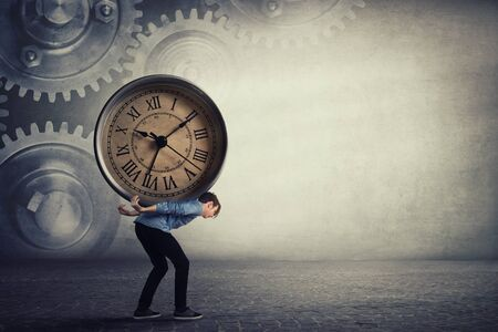 Bent down guy carrying a big heavy clock on his back. Overloaded student tired of daily tasks, and difficult burden. Time pressure and management concept, schedule efficiency, planning and control.