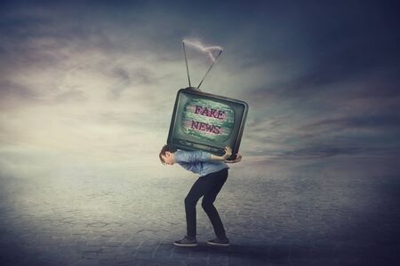Bent down guy carrying an old TV box on his back. Overloaded man bored of daily fake news on television has a difficult burden. Mass media manipulation and brainwashing concept, propaganda control. Stok Fotoğraf