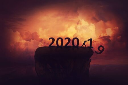 Farewell to the old 2019 and hello to the new 2020 year. Holiday scene concept with a man announcing a new start, ready for change and challenges, pushing down of a cliff the previous 19 year numbers.