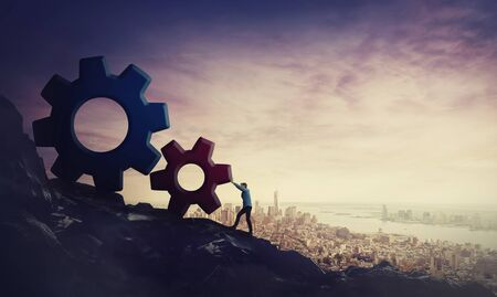 Surreal scene determined businessman pushing big cog wheels uphill. Business concept, hard working for purpose fulfilling and success achievement. Climbing a tall mountain over city horizon background