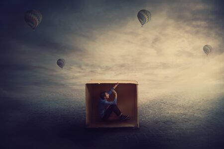 Surreal scene as a trapped guy want to get out of a cardboard package, needs to think outside the box. Scared man caged by own fears sitting inside a carton hut. Introvert and extrovert concept.