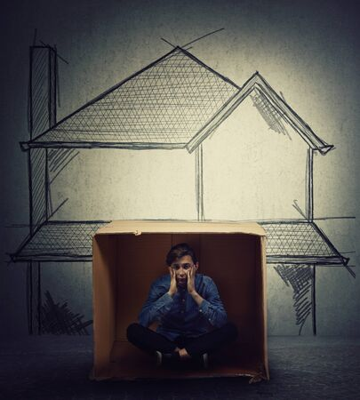 Stressed teenage boy sitting inside a cardboard box hut, imagine a big house. Improvised shelter of homeless and refugees. Poverty and homelessness concept as beggar child dreams of own home. Stok Fotoğraf