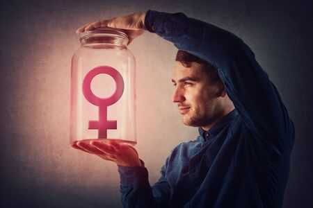 Young male, malefic look holding a glass jar with female gender symbol inside as captive. Man pretending to be superior to woman, gender gap idea, sex inequality concept. Social issue, discrimination.