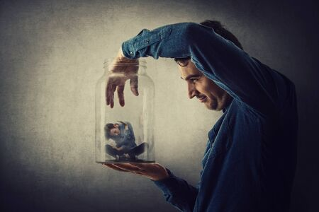 Conceptual scene, scared tiny boy trapped inside a glass jar held in hand by a scary giant. Surreal nightmare, child adoption through the eyes of a teen. Helpless captive kid victim of family abuse.