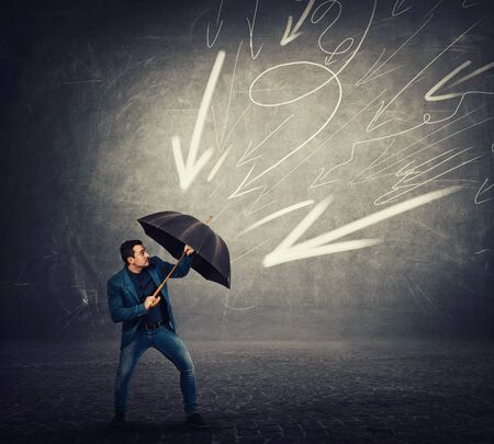 Determined businessman hiding behind umbrella as a shield to protect of any danger and high pressure of arrow sketches pointed to him. Business concept of facing adversity and auto defending.