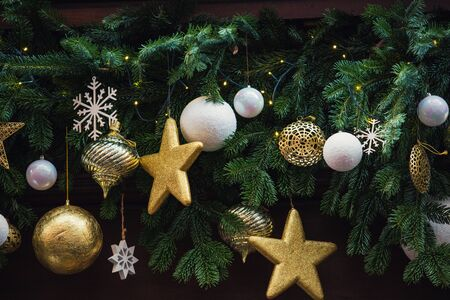 Different decorations hanging on the fir tree branches as lights, globes, stars and snowflakes symbolizing the beautiful atmosphere of winter holidays. Christmas and new year celebration background. Stok Fotoğraf