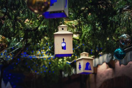 Blue light lantern like Christmas decorations and globes hanging on green fir tree branches above the street. Beautiful outdoors atmosphere before winter holidays. Stok Fotoğraf
