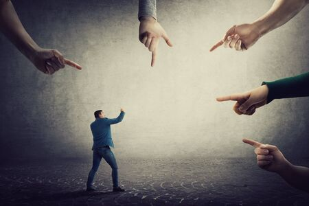 Frustrated businessman starts fighting against people blaming him. Self defense concept, guy fight for truth and justice, being under pressure as multiple index fingers pointing to him.