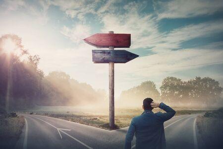 El empresario trasero frente a la encrucijada y las flechas de señalización muestran dos cursos diferentes, dirección izquierda y derecha para elegir. La carretera se divide en distintas direcciones. Decisión difícil, concepto de elección.