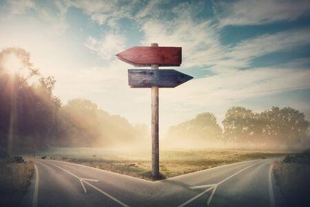 Paisaje surrealista con una carretera dividida y flechas de señalización que muestran dos cursos diferentes, dirección izquierda y derecha para elegir. La carretera se divide en distintas direcciones. Decisión difícil, concepto de elección. Foto de archivo