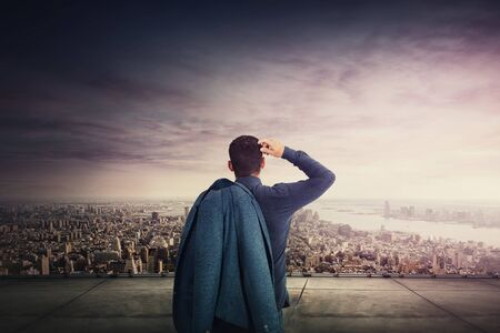 Rear view of pensive businessman standing on the rooftop of a skyscraper watching the city skyline. Motivated manager gaining inspiration for future projects. Business career planning concept.