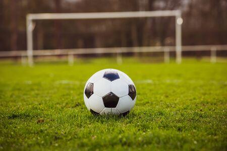 Modello tipico in bianco e nero tipico del pallone da calcio, disposto sul tappeto erboso dello stadio. Pallone da calcio tradizionale sul prato di erba verde con spazio di copia.