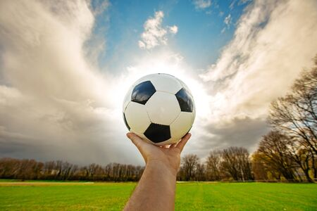 Hand holding classic soccer ball in sunset  with typical black and white pattern. Young man holding traditional football ball over sky background. with copy space.