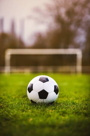 Classic soccer ball in sunset  with typical black and white pattern, placed on stadium turf. Traditional football ball on the green grass lawn with copy space. Stock Photo