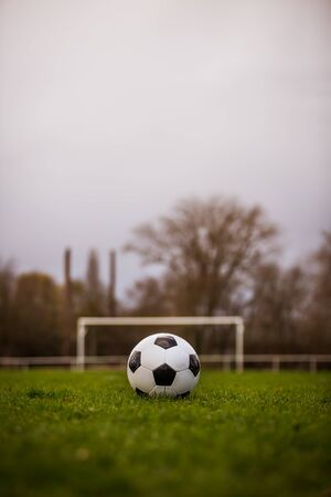 Classic soccer ball  with typical black and white pattern, placed on stadium turf. Traditional football ball on the green grass lawn with copy space.