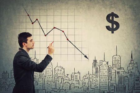 Businessman analyst gives pessimistic prognosis of COVID-19 impact to the future world economics, drawing decline graph of stock market. Global finance collapse, recession concept. Real estate crisis. Banco de Imagens