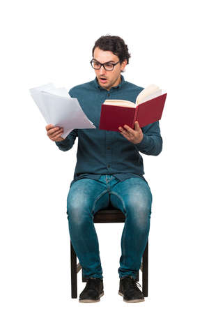 Full length of perplexed student looking stunned at paper projects and book in his hands, seated on chair isolated on white. Bewildered man wears glasses, looking confused at a textbook and sheets.
