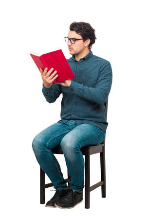 Full length student reading a book, seated on chair isolated on white background. Casual man reader wears glasses, looking contented, learning from home. Studying process, education concept. Banco de Imagens
