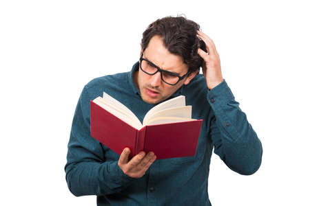 Puzzled man reading a book, scratching his head, isolated on white background. Student or professor wears eyeglasses looking confused in a textbook. Education concept, studying and learning home.