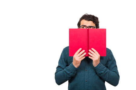 Student guy hiding behind a red book, looking suspicious aside isolated on white background with copy space. Scared nerd person, wearing eyeglasses, try to be invisible or incognito, covers face. Banco de Imagens