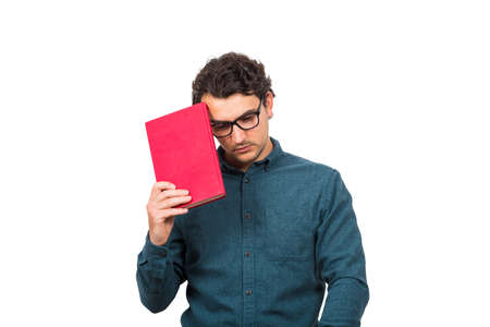 Pessimistic student guy looking down upset, as holds a book isolated on white background. Confused young man has learning troubles, negative face expression, study problems, education concept. Banco de Imagens