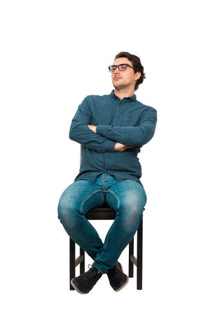 Full length portrait of confident businessman seated relaxed on a chair, wearing eyeglasses and keeps arms crossed, isolated on white background. Contented business person, looking determined aside.
