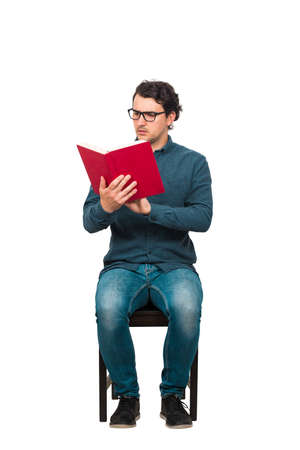 Full length of puzzled man reading a book seated on chair isolated over white background. Student or professor wears glasses looking confused at a textbook. Education concept, study and learning home. Banco de Imagens