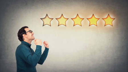 Overjoyed businessman keeps fists tight, celebrate success achievement, as receives positive feedback and approval. Boss, company owner cheerful as earns five stars rating excellent customer service.