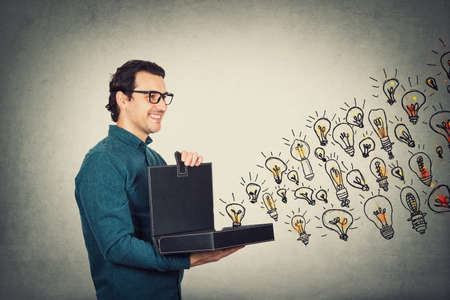 Businessman opens his briefcase filled with brilliant ideas as different lightbulbs comes out of the box. Ingenious boss shows the business portfolio, shares his creativity and genius with employees. Standard-Bild