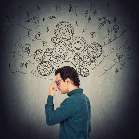 Side view portrait of pensive businessman, keeps index finger to forehead, thinking of solutions to solve the task. Pondering man focuses his mind. Gear cogwheels and arrows as thoughts around head.