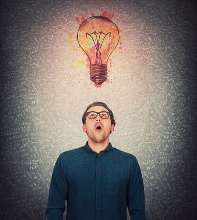 Amazed businessman, wears eyeglasses, big eyes looking up astonished, as a colorful light bulb shine bright above head. Eureka idea concept, surprised guy open mouth expression, staring upwards. Stock Photo